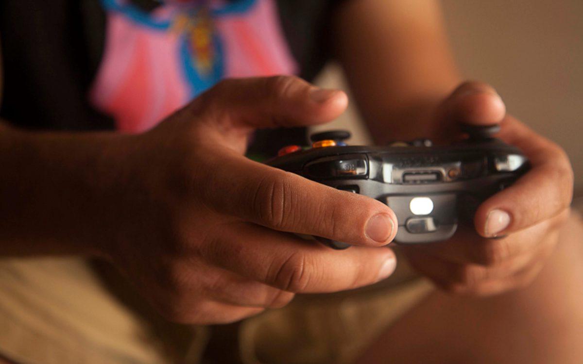 Mão segurando um controle de vídeo game