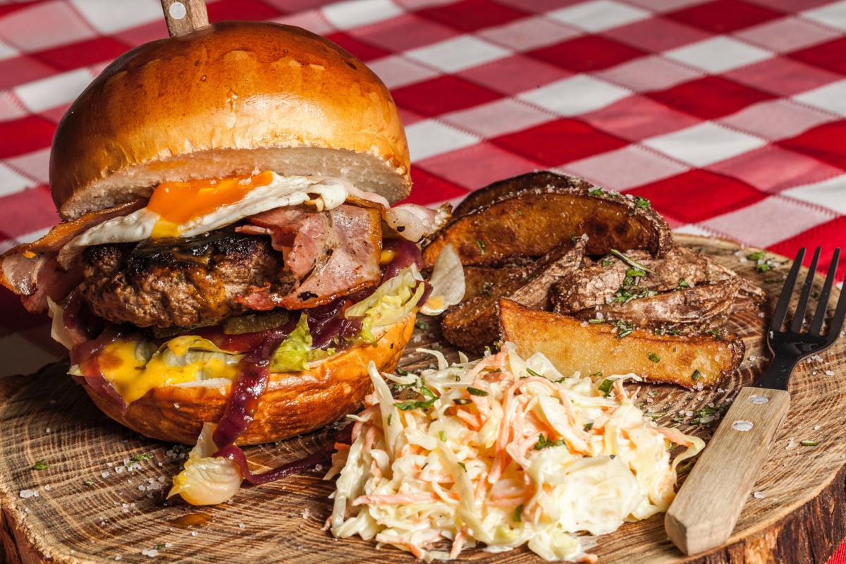 Tábua de madeira com um lanche de hambúrguer, costela desfiada e algumas outras carnes. Tudo parece muito delicioso.