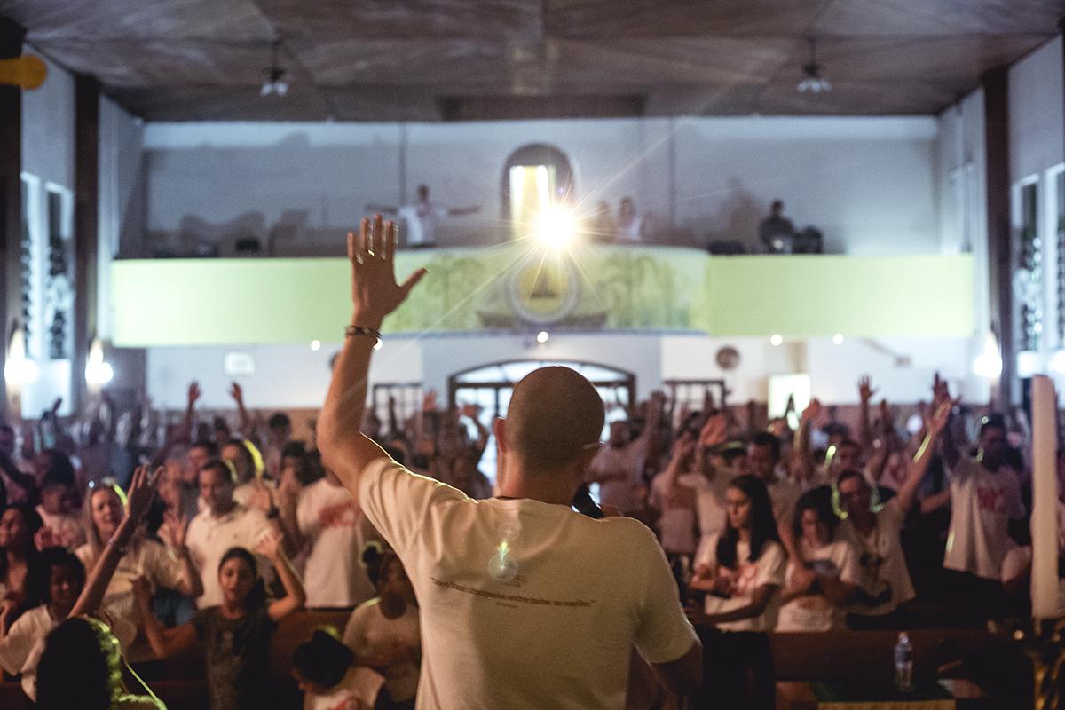 Guilherme Maggio de costas para a câmera e voltado para o povo dentro de uma Igreja num momento de oração e louvor. Sua mão esquerda está levantada. O povo à sua frente está em oração da mesma maneira, inclusive alguns com as mãos levantas.