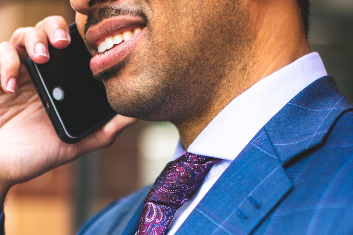 Homem negro usa terno azul, camisa branca e gravata roxa. Ele fala ao telefone com uma expressão de desgosto. O close está entre seus lábios e o nó da gravata