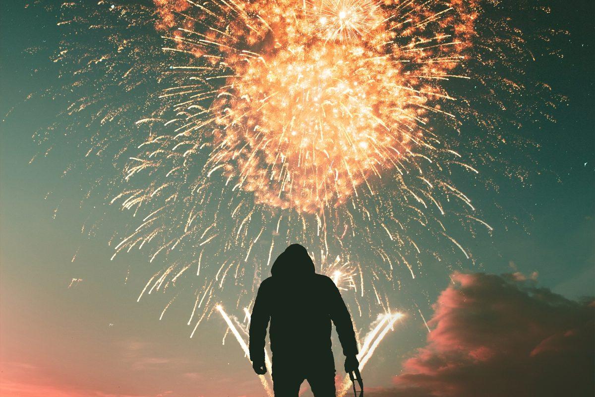 Sombra de homem que está de pé olhando para os fogos estourando no céu (em destaque)